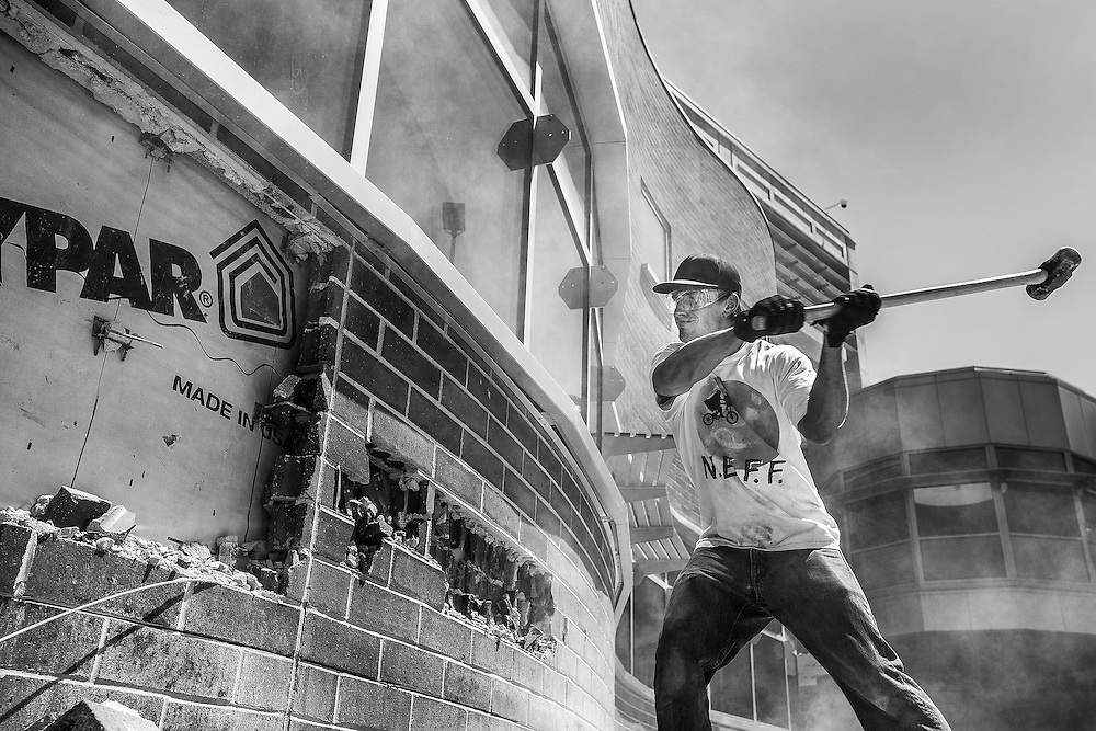 Construction worker knocks brick off the wall as part of the preparations for the Holdman Windows project currently underway at the UVU Library on the Campus of Utah Valley University in Orem, Utah Monday August11, 2014. (August Miller)