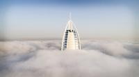Aerial view of the luxurious Burj Al Arab hotel crossing the clouds of Dubai, U.A.E.
