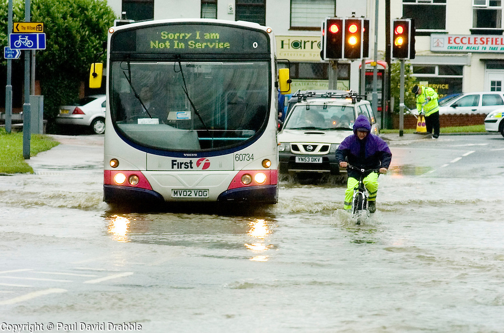 Torrential rain causes flooding and traffic chaos as a cyclist braves the floods and gridlock with what appears to be better results than many car drivers.on The Common Ecclesfield Sheffield South Yorkshire.25 June 2007.Image COPYRIGHT Paul David Drabble.