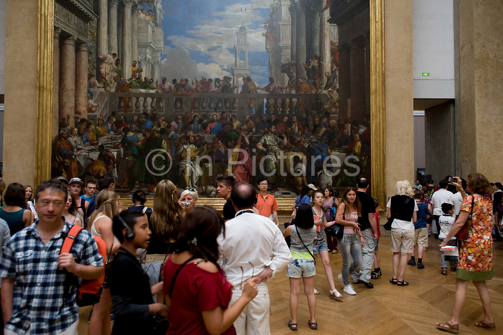 Tourists mingle beneath the Wedding at Cana (or The Wedding Feast at Cana), a massive painting by the late-Renaissance or Mannerist Italian painter, Paolo Veronese - on display in the Musée du Louvre in Paris, where it is the largest painting in that museum's collection. The Musée du Louvre is one of the world's largest museums, the most visited art museum in the world and a historic monument. A central landmark of Paris, France, it is located on the Right Bank of the Seine in the 1st arrondissement (district). Nearly 100,000 objects from prehistory to the 19th century are exhibited over an area of 60,600 square metres (652,300 square feet).