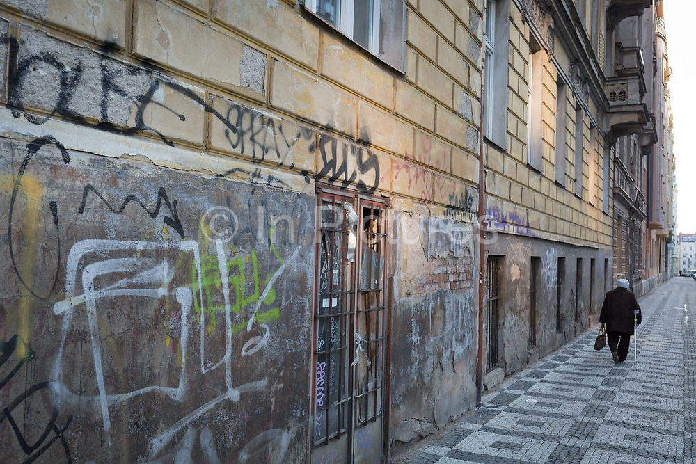 An elderly woman walks down a long street of graffiti, a closed business and old render in the Holesovice district, Prague 7, on 20th March, 2018, in Prague, the Czech Republic.