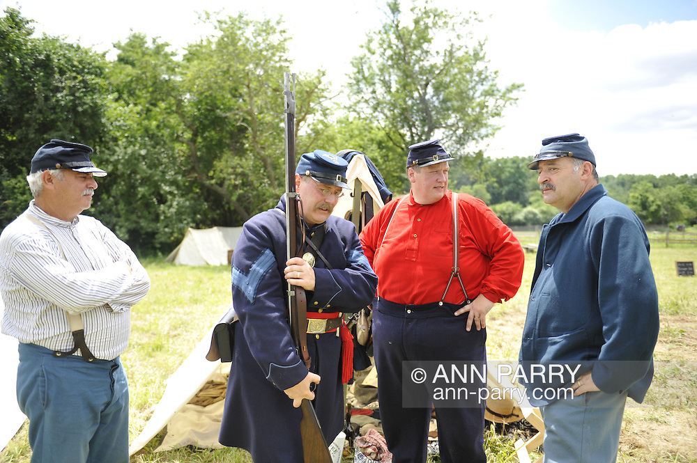 Old Bethpage, New York, USA - July 21, 2012:  Left to right, NEIL YANK of Levittown, NY; MIKE SCALLION of Dix Hills, NY; ROBERT WALKER of Coram, NY; and GENE MONGELLO of Levittown, NY, portray soldiers at re-creation of Camp Scott, a Union Army training camp, at Old Bethpage Village Restoration, to commemorate 150th Anniversary of American Civil War, on Saturday, July 21, 2012.