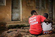 A woman wearing a t-shirt promoting the end of female genital mutilation sits with a teenage girl in Katiola, Cote d'Ivoire on Saturday July 13, 2013.