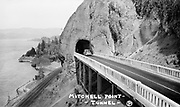 """1307C-85. """"Mitchell Point tunnel."""" The Mitchell Point tunnel and viaduct were located 4 miles west of Hood River. It was circumvented by a water-level road in 1954. The tunnel and viaduct were blasted away during an I-84 widening project in 1966."""