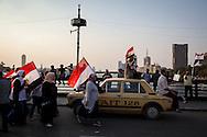Anti government protestors in Egypt walk over the river Nile on a bridge leading to Tahrir square