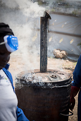 30 May 2019, Mokolo, Cameroon: Biomass burns in a metal container as part of the process towards becoming charcoal. At the Minawao camp for Nigerian refugees, degradable and non-degradable waste are separated, so that biomass can be burnt in metal containers, processed and finally transformed into charcoal briquettes as a source of recycled energy to be used as firewood for cooking. With the support of an environment monitor  from the Lutheran World Federation World Service programme, the full process from waste to charcoal is managed and run by the refugees themselves. The Minawao camp for Nigerian refugees, located in the Far North region of Cameroon, hosts some 58,000 refugees from North East Nigeria. The refugees are supported by the Lutheran World Federation, together with a range of partners.