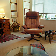 A large brown leather chair in a plain room, with Oriental carpets and small footrest on a plain beige rug. There is a large circular glass table in the foreground, windows to the left and behind the chair, a wooden desk and chair to the left rear, and diplomas on the back wall.