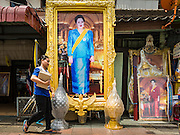 10 AUGUST 2016 - BANGKOK, THAILAND: A Thai woman walks past a portrait of Queen Sirikit of Thailand. Thais are preparing for the Queen's birthday. Queen Sirikit of Thailand, was born Mom Rajawongse Sirikit Kitiyakara on 12 August 1932. She married  Bhumibol Adulyadej, King of Thailand (Rama IX) in 1950. He is the longest serving monarch in the world and she is longest serving consort of a monarch. Her birthday, like the King's Birthday (which falls on Dec. 5),  is a national holiday in Thailand. Her birthday, August 12, is also celebrated as Mothers' Day in Thailand. Thais hang portraits of Queen Sirikit in their homes and fly her royal flag on her birthday.        PHOTO BY JACK KURTZ
