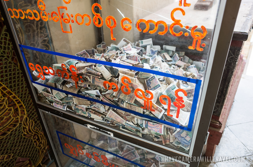 "A cash-filled donation box at the Myazedi (or Mya Zedi) Pagoda, in the northern part of Myinkaba Village, just woth of Old Bagan. Myazedi translates as ""emerald stupa."""