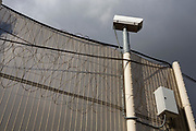 A security camera sits above large metal security gates of an internal secure fence that surrounds a wing and exercise yard of HMP Pentonville, London, UK. (Photo by Andy Aitchison)