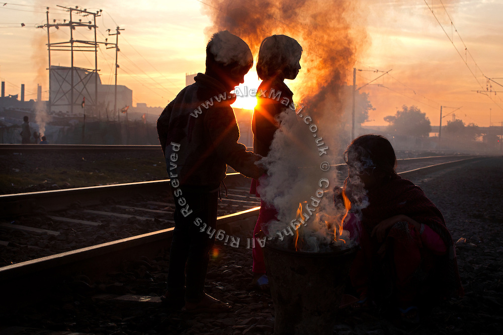 Warming up during a cold morning, three siblings are sitting by the fire in front of their home by the railway tracks in New Arif Nagar, one of the water-affected colonies standing next to the abandoned Union Carbide (now DOW Chemical) industrial complex, site of the infamous 1984 gas tragedy in Bhopal, Madhya Pradesh, central India. The poisonous cloud that enveloped Bhopal left everlasting consequences that today continue to consume people's lives.