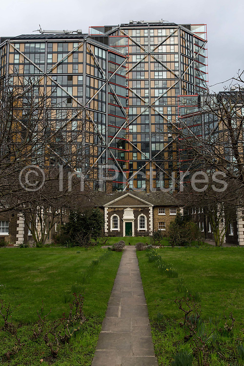 21st Century architecture towers over the impressive Hopton Gardens Almshouses on 19th February on Hopton Street, Southwark, London, United Kingdom. Adjacent the Tate Modern, Hoptons Almshouses offers a glimpse into life on Bankside over 250 years ago. Built between 1746–49 by Thomas Ellis and William Cooley. The cottages have been continuously occupied and after modernisation in 1988, and additional renovation in 2013, 20 1-bedroomed units have been available for Southwark residents over 60 who have lived in the borough for at least three years.  Hopton's Almshouses are managed by the United St Saviour's Charity, a long established charity that has its roots in the 16th century.