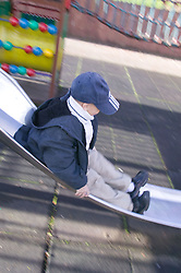 Little boy sliding down a slide in the playground,