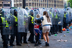 Glasgow, Scotland, UK. 15 May 202. Rangers football supporters  celebrating 55th league victory are cleared from George Square by police in riot gear on Saturday evening. In very violent scenes police were pelted with bottles and items from a nearby construction site as police pushed the supporters into the south west corner of the square. Pic; two females attempt to leave area through police line. Iain Masterton/Alamy Live News.