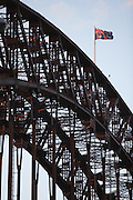 Detail of Sydney Harbour Bridge with flag lit by afternoon sun