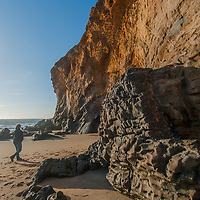 A hiker walks past colorful eroded sedimentary rocks by Panther Beach, north of Santa Cruz, California.