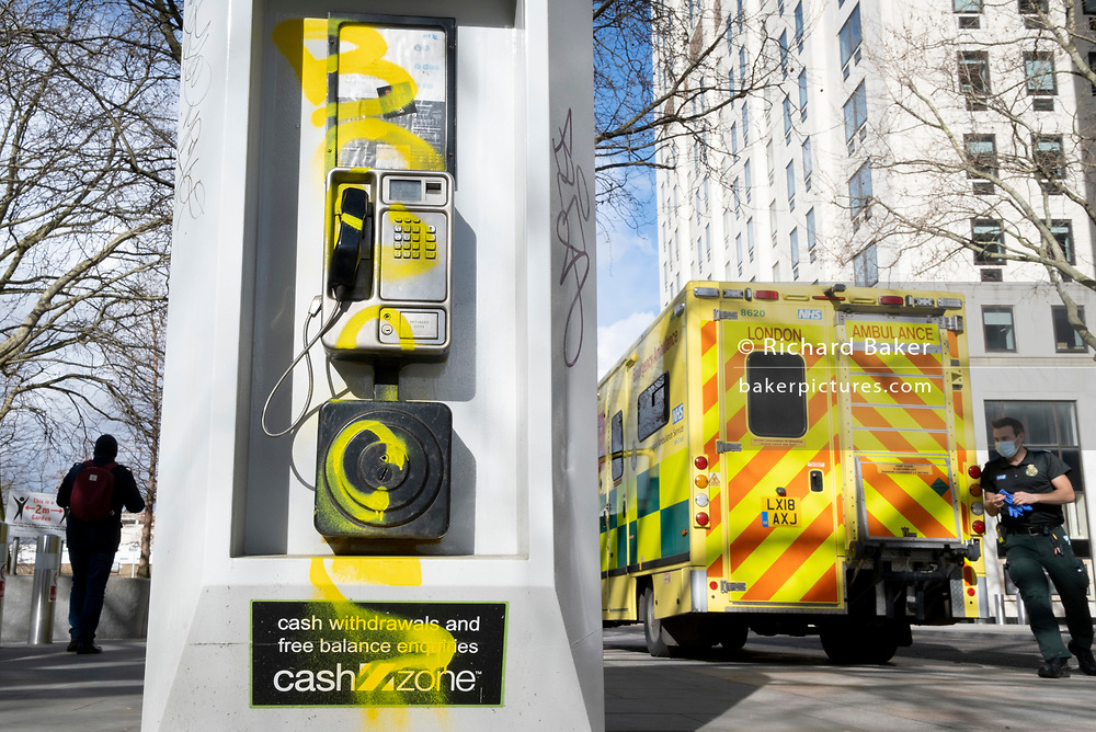 An NHS (National Health Service) paramedic prepares to attend an nearby emergency, at the rear of his ambulance, stopped alongside a public BT landline phone kiosk which has been vandalised by the spraying of yellow aerosol paint over its handset and keypad on the Southbank in Waterloo, on 11th March 2021, in London, England.
