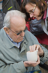 Visually impaired people with carers on outing to Denby Pottery. Touching jug.