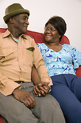 Older couple together at home; smiling,
