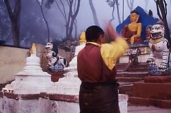 Asia, Nepal, Kathmandu, Buddhist monk lifts arms in prayer at base of Swayambhunath Stupa in fog