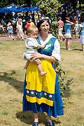 Woman dressed in Swedish costume holding baby. Svenskarnas Dag Swedish Heritage Day Minnehaha Park Minneapolis Minnesota USA