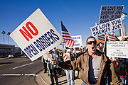 """15 DECEMBER 2007 -- PHOENIX, AZ: Anti immigration protestors gather on a street corner in central Phoenix, AZ. The corner of 35th Street and Thomas Road in Phoenix has emerged as """"Ground Zero"""" in the immigration debate in Arizona. A furniture store at the intersection has hired off duty sheriff's deputies to arrest day laborers who used to gather near there for loitering. Pro immigrant groups have labored the move racist while anti-immigrant groups call it law abiding and patriotic. Every week, hundreds of people gather on opposite corners of the intersection to chant and hurl insults at each other.  Photo by Jack Kurtz"""