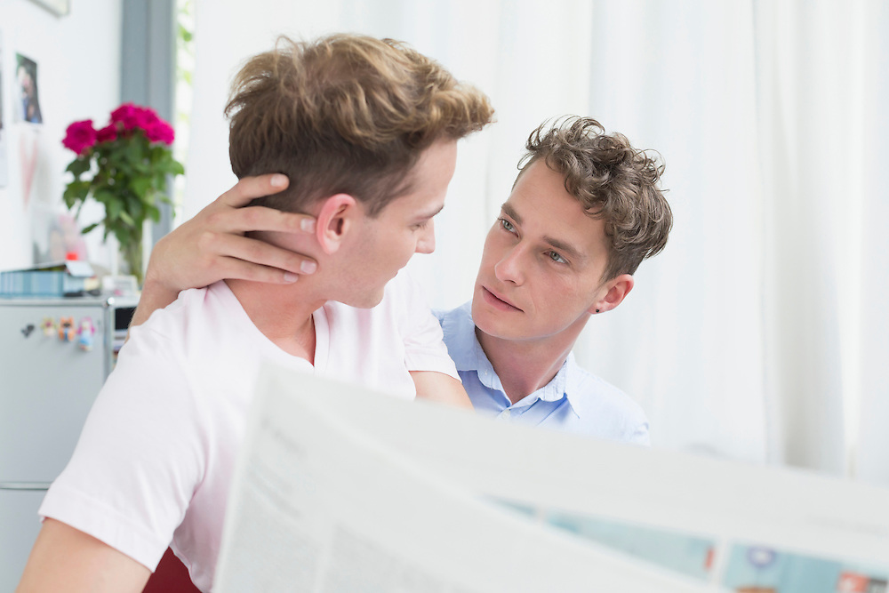 Homosexual couple embracing each other while reading newspaper