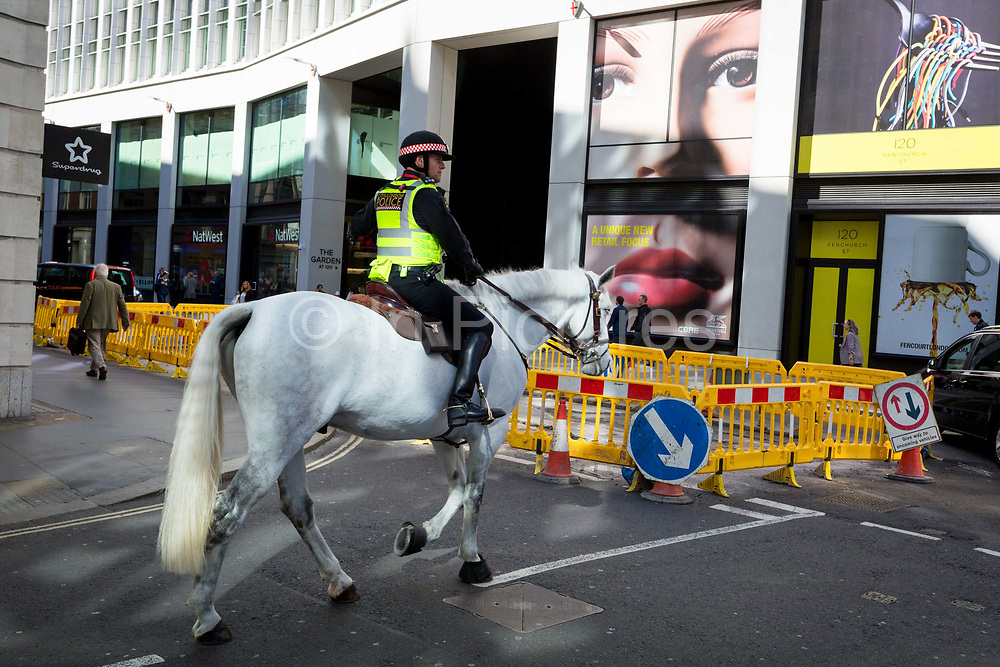 A pair of eyes and a mounted City police officer on Fenchurch Street - in the heart of the capitals financial district aka The Square Mile,  on 25th September 2018, in London, England.