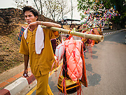 "05 APRIL 2015 - CHIANG MAI, CHIANG MAI, THAILAND: A Tai Yai man carries baskets that represent a novice's personal belongings during a parade of Buddhist novices parade through the streets of Chiang Mai on the second day of the three day long Poi Song Long Festival in Chiang Mai. The Poi Sang Long Festival (also called Poy Sang Long) is an ordination ceremony for Tai (also and commonly called Shan, though they prefer Tai) boys in the Shan State of Myanmar (Burma) and in Shan communities in western Thailand. Most Tai boys go into the monastery as novice monks at some point between the ages of seven and fourteen. This year seven boys were ordained at the Poi Sang Long ceremony at Wat Pa Pao in Chiang Mai. Poy Song Long is Tai (Shan) for ""Festival of the Jewel (or Crystal) Sons.    PHOTO BY JACK KURTZ"