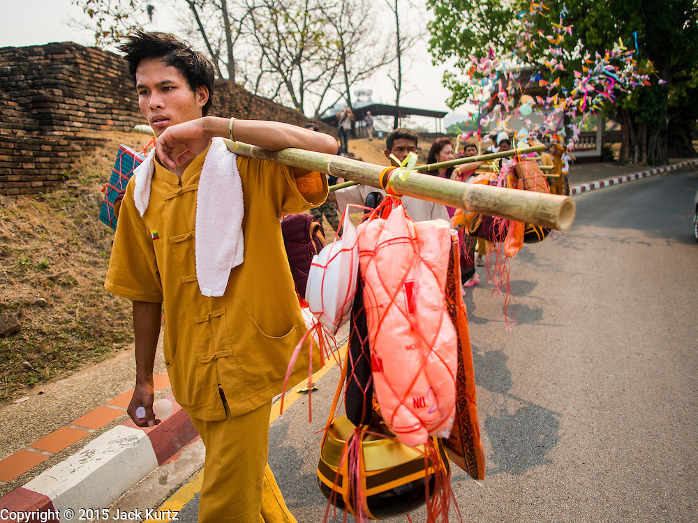 """05 APRIL 2015 - CHIANG MAI, CHIANG MAI, THAILAND: A Tai Yai man carries baskets that represent a novice's personal belongings during a parade of Buddhist novices parade through the streets of Chiang Mai on the second day of the three day long Poi Song Long Festival in Chiang Mai. The Poi Sang Long Festival (also called Poy Sang Long) is an ordination ceremony for Tai (also and commonly called Shan, though they prefer Tai) boys in the Shan State of Myanmar (Burma) and in Shan communities in western Thailand. Most Tai boys go into the monastery as novice monks at some point between the ages of seven and fourteen. This year seven boys were ordained at the Poi Sang Long ceremony at Wat Pa Pao in Chiang Mai. Poy Song Long is Tai (Shan) for """"Festival of the Jewel (or Crystal) Sons.    PHOTO BY JACK KURTZ"""
