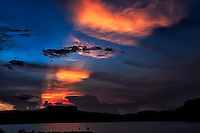 El Yunque: As fishermen attempt the last catch of the evening, the mountain of El Yunque appears to have vivid sun-rays pulsating from its silhouetted flat top, Baracoa Cuba.