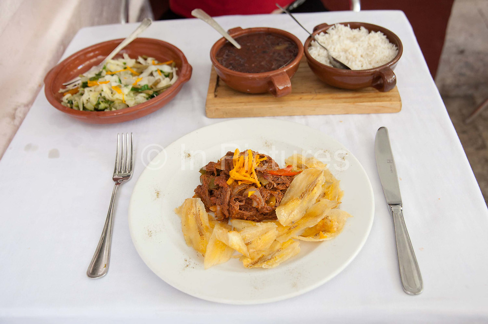 Ropa Vieja, which literally translated means old Clothes, is a traditional Cuban dish made of beef and served with plantain chips. This is an excellent example from Paladar Dona Eustacia in the Cathedral Square in Havana old town.