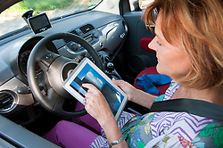 Senior woman sitting in car and using digital tablet