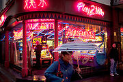 Night time scene outside an amusements arcade in Chinatown. Here people can bet on small gaming machines andplay on video games.