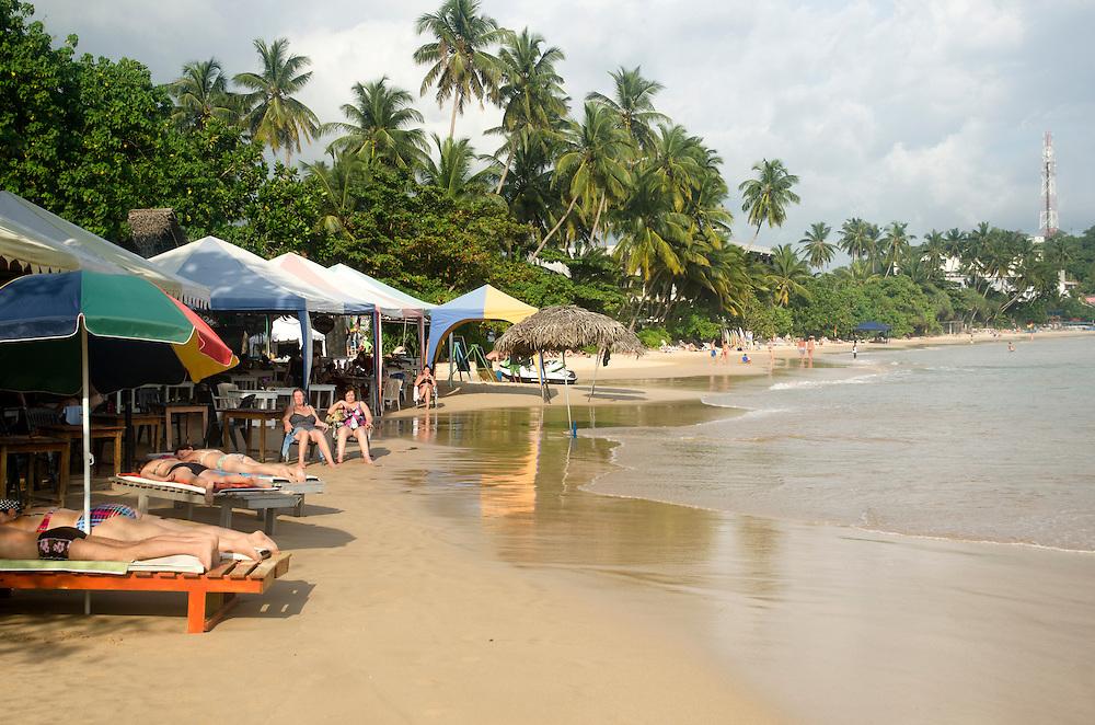 Tourists relax on Mirissa beach, Sri Lanka