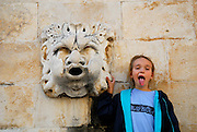 Child (9 years old) with stone gargoyle, Dubrovnik old town, Croatia