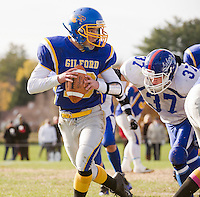 Gilford quarterback Carter Mercer gets pressure from Interlakes Evan Candage as he looks for the pass during Saturday's NHIAA Division III North semi final conference game at the Meadows Field.  (Karen Bobotas/for the Laconia Daily Sun)