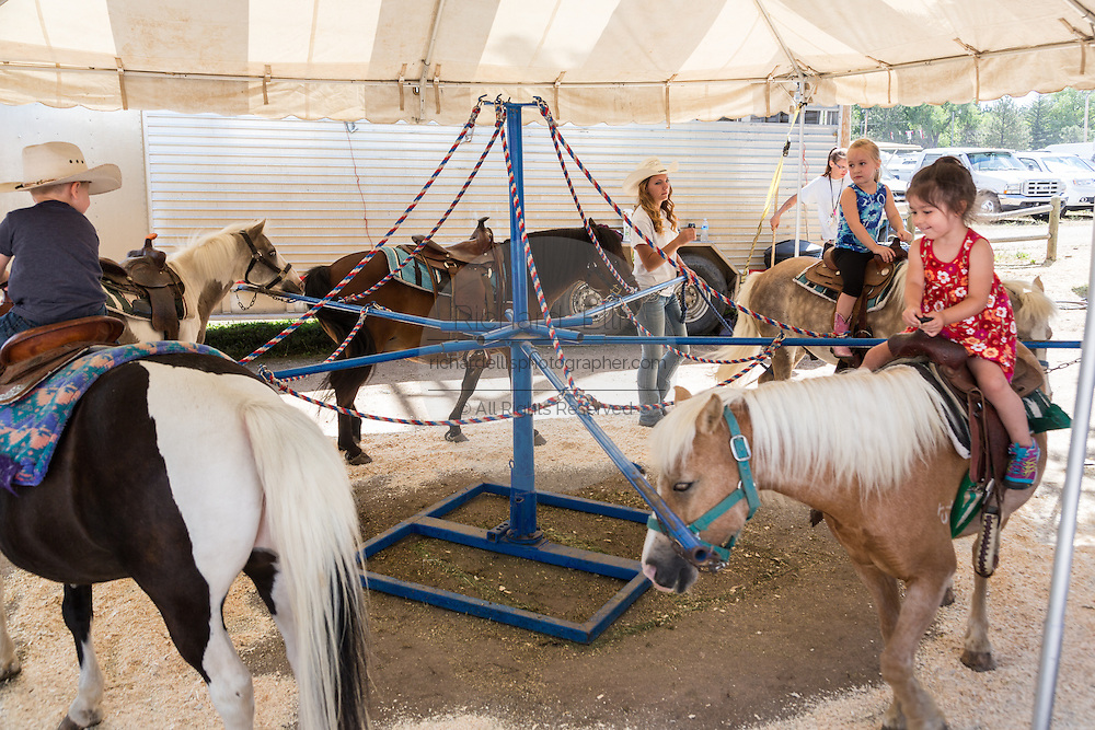 Children ride ponies during Cheyenne Frontier Days July 25, 2015 in Cheyenne, Wyoming. Frontier Days celebrates the cowboy traditions of the west with a rodeo, parade and fair.