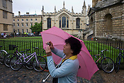A chinese tourist photographs architecture in Radcliff Square, Oxford University.