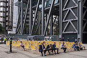 City workers watch a womens' tennis match on a huge screen outside the City of London headquarters of insurance company Aviva during Wimbledon fortnight, on 4th July, London, United Kingdom. Businessmen sit in deck chairs eating their lunches while the tennis is broadcast for the general public seated beneath the struts and girders of large financial institutions on Fenchurch Street. (Photo by Richard Baker / In Pictures via Getty Images)