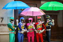 © Licensed to London News Pictures. 20/11/2016. London, UK. Performers dressed as Power Rangers take shelter from the rain as over 400 cast members get ready to participate in Hamley's Toy Parade, which marches along Regent Street in London in a colourful extravaganza, with marching bands, dancers and toy vehicles. Photo credit: Tolga Akmen/LNP
