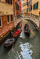Gondolas ply a route along a back canal, Venice, Italy.