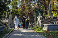 Nuns are on their way to graves with flowers and cleaning supplies at Rakowicki cemetery in Krakow, Poland 2019.