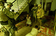 Soldiers question a man about weapons in the area.