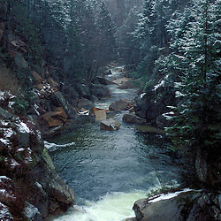 Light snow falls along New Hampshire's Pemigewasset River in Franconia Notch State Park.  Near The Flume, NH