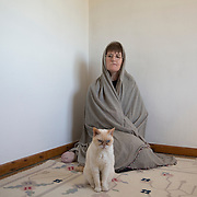 Hermit Sister Rachel Denton sits with a cat in a prayer shawl at St Cuthberts' Hermitage in Lincolnshire, north east Britain April 27, 2015. Sister Rachel Denton has vowed to spend the rest of her life living as a consecrated hermit in the Catholic faith. A hermit is a person who chooses to live alone, with the intention of finding God. Rarely leaving her house she lives a life of prayer and solitude. However, she uses the internet and social media to share her experience and distance her self from physically interacting with society. REUTERS/Neil Hall