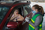 Helen McCauley, left, of New Tripoli, talks to registered nurse Caroline Spalding, right, during a COVID-19 drive-through vaccination clinic put on by Lehigh Valley Health Network on Jan. 27, 2021, at Dorney Park in Allentown, Pennsylvania. Community members 75 and older were eligible to receive their first dose with an appointment ahead of time.