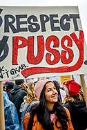 """A woman smiles up at her sign reading, 'Respect pussy,"""" the second word highlighted in red glitter."""