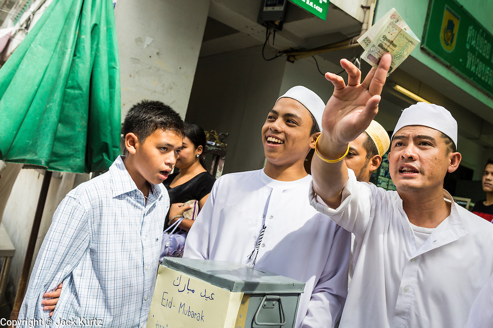 """08 AUGUST 2013 - BANGKOK, THAILAND: Thai Muslim men ask for donations for Haroon Mosque after Eid al-Fitr services at the mosque. Eid al-Fitr is the """"festival of breaking of the fast,"""" it's also called the Lesser Eid. It's an important religious holiday celebrated by Muslims worldwide that marks the end of Ramadan, the Islamic holy month of fasting. The religious Eid is a single day and Muslims are not permitted to fast that day. The holiday celebrates the conclusion of the 29 or 30 days of dawn-to-sunset fasting during the entire month of Ramadan. This is a day when Muslims around the world show a common goal of unity. The date for the start of any lunar Hijri month varies based on the observation of new moon by local religious authorities, so the exact day of celebration varies by locality.      PHOTO BY JACK KURTZ"""