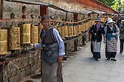 Tibetan pilgrims turn prayer wheels as they follow the kora around the Potala Palace in Lhasa.